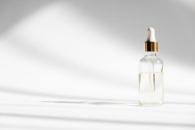 ドロッパーガラスボトルモックアップ。白い背景の上の化粧品のピペット。
