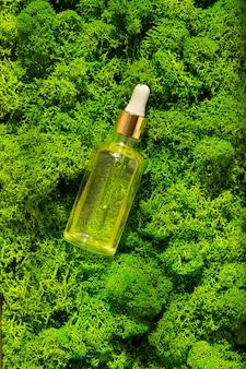 グリーンモスバックグラウンドボディトリートメントとスパナチュラルビューティー製品のドロッパーガラスボトルモックアップエコクリームセラムスキンケアブランクボトルアンチセルライトマッサージオイルオイリー化粧品ピペット