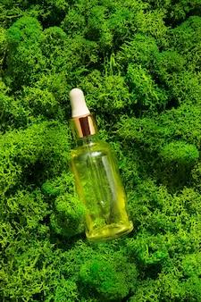 緑の苔の背景のボディトリートメントとスパの自然の美容製品のスポイトガラス瓶のモックアップ...