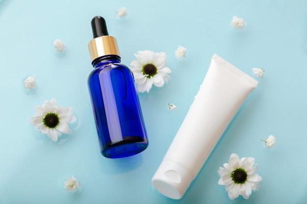花のある青い水面にスポイトセラムとチューブ化粧品。スキンケア水分バランスのためのフェイス化粧品。アクアクリームチューブとコラーゲンまたはヒアルロン酸血清。