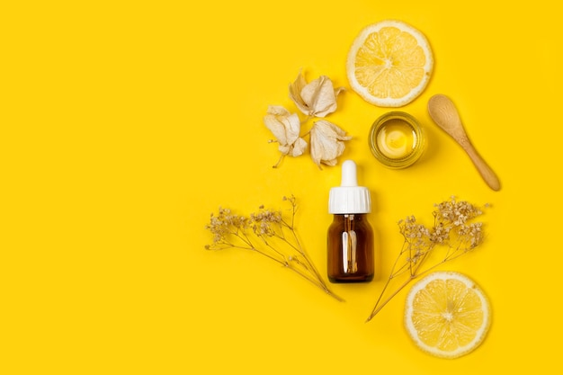 A dropper of skin oil on a yellow background in a top view