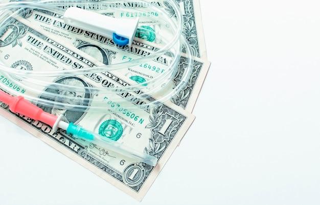 Капельница с долларами на белом фоне. концепция лечения и здоровья.