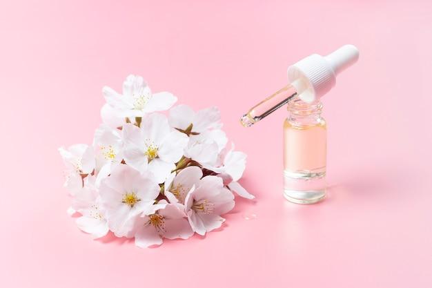 Капельница с маслом и цветами вишни на розовом фоне, концерт натуральной косметики