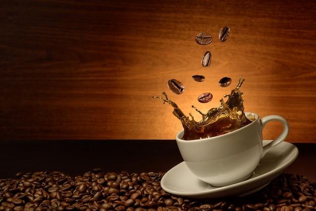 커피 컵에 커피 콩을 떨어뜨리다