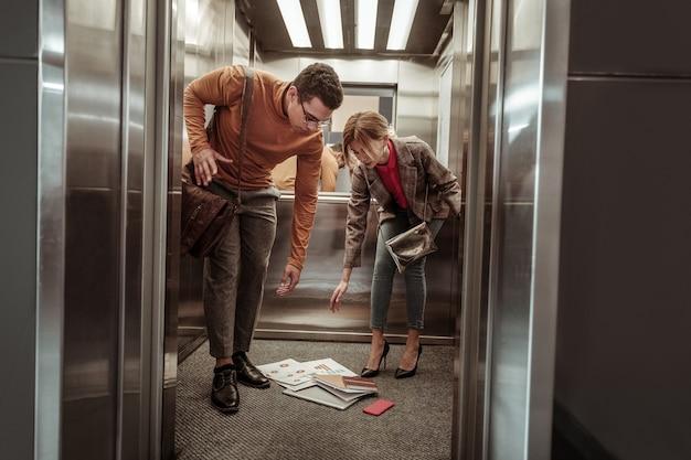 Отбрасывание бумаг. услужливый темноволосый парень помогает своей женщине после того, как сбросил бумаги в лифте