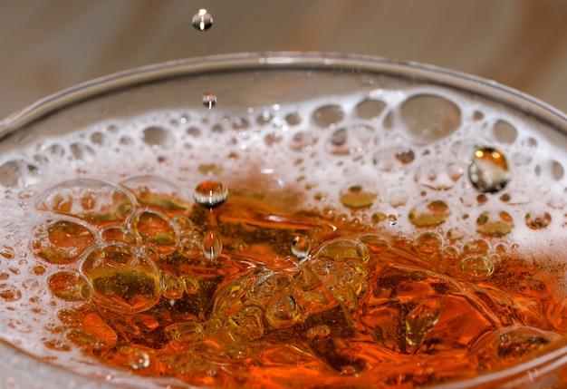 Капли и пузыри светлого пива в стеклянной пуле выстрелил макросъемку крупным планом