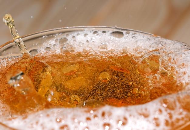 ガラスの弾丸ショットのクローズアップマクロ写真で軽いビールの滴と泡