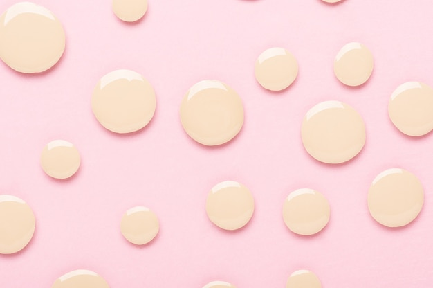 Drops of foundation for makeup on a pink textured background top view. sample smeared with liquid fluid for flat lay contouring. beige bb cream. cosmetic concealer for perfect face correction.