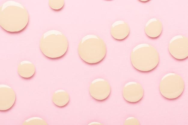 분홍색 질감 배경 상단 보기에서 메이크업을 위한 기초 한 방울. 평평한 윤곽 윤곽을 위해 액체 액체로 얼룩진 샘플. 베이지색 비비크림. 완벽한 얼굴 보정을 위한 코스메틱 컨실러.