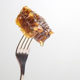 Капли свежего меда стекают с воскового меда на столовую вилку. витаминное питание и продукты пчеловодства