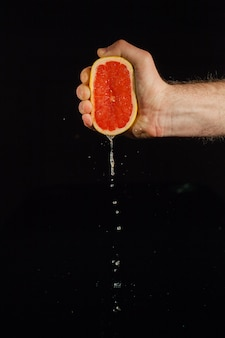 Drops of grapefruit juice fall from fruit on black background