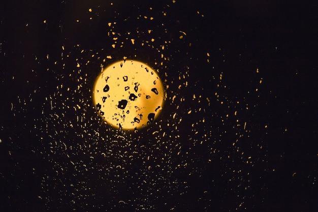 밤에 어두운 유리에 달의 비와 빛 방울.