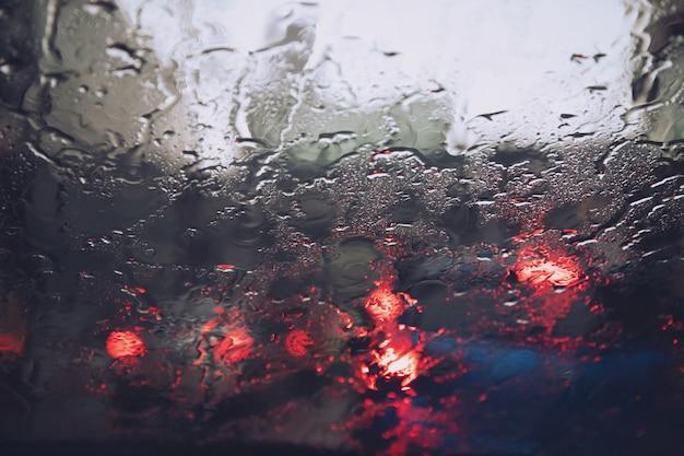 夕方にはガラスのフロントガラスに雨のしずくが降り注ぐ。大雨の中の通り。市内のテールライトと信号機。
