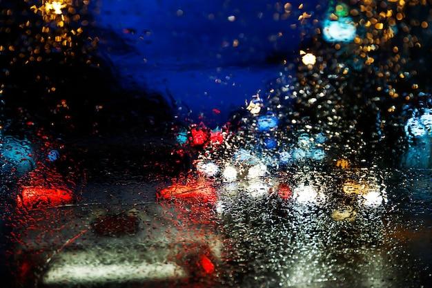 밤에 유리 앞유리에 이슬비가 내립니다. 폭우에 거리입니다. 보케 테일 라이트. 소프트 포커스. 미끄러운 길 조심히 운전하세요. 소프트 포커스. 교통 체증 차.