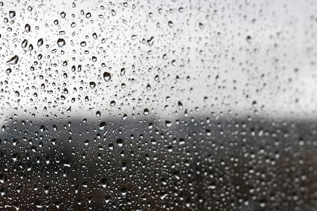 Капли воды на стекле на размытом фоне темного светлого градиента