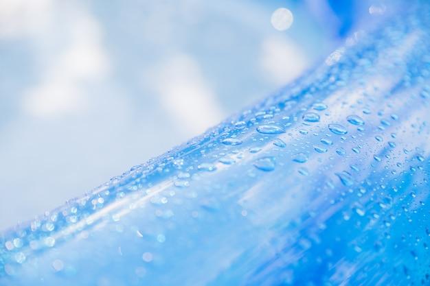 Капли воды - на синей поверхности надувного игрушечного колеса. надувной пляжный матрас с каплями воды в солнечный день. яркая голубая поверхность детского бассейна с каплями воды на нем. летний бассейн