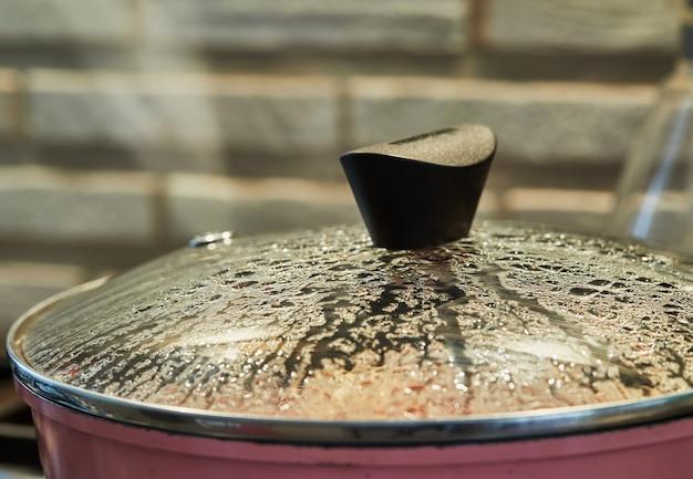 Капли на стеклянной крышке сковороды готовят блюдо в духовке с селективным фокусом