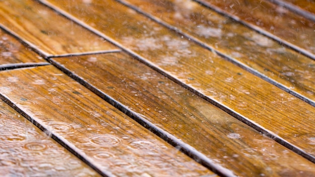 Drops of rain fall on a wooden terrace and a bridge near the pool close up