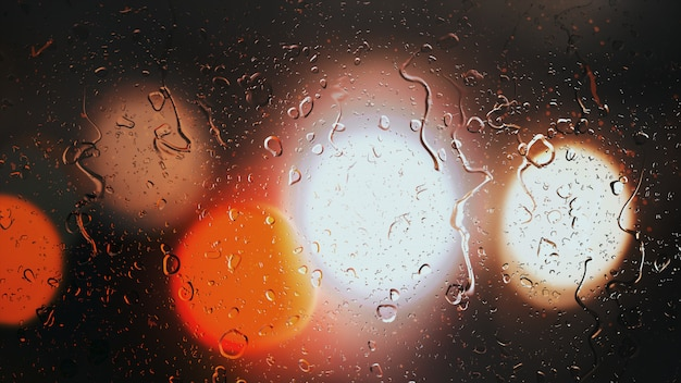 Drops of rain flow down the glass against the bokeh background of moving cars
