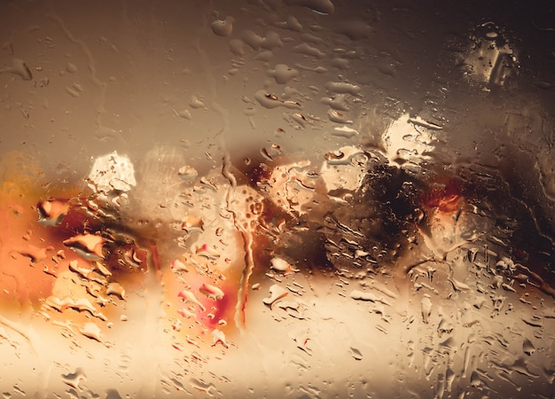 Drops of rain wiht street bokeh lights out of focus autumn abstract backdrop