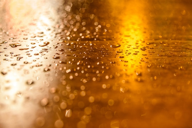 Drops of rain on a wooden table illuminated by streetlights one night.