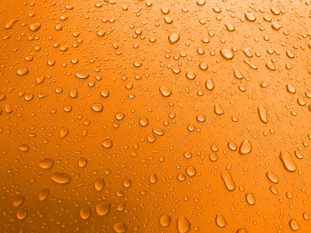 Drops of water on an orange metal surface, beautiful background after rain