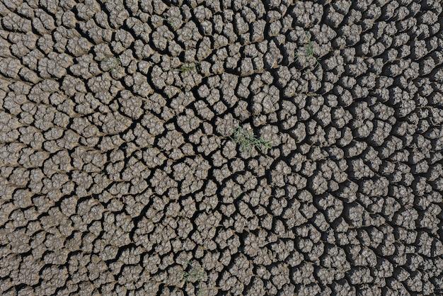 Засуха глубоко потрескавшаяся поверхность земли, освещенная солнцем