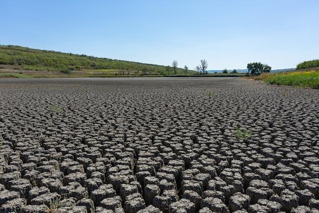 Засуха глубоко потрескавшаяся земля под голубым небом