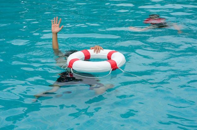 Утопающий поднимает руки за помощь в бассейне,