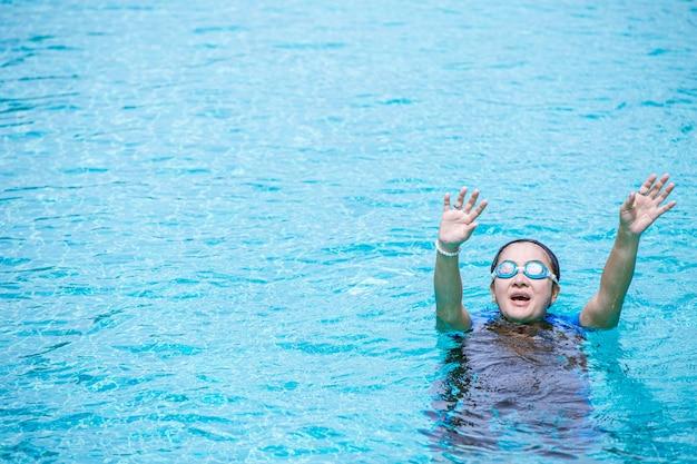 水泳中にけいれんを起こしている女性を溺れさせ、テキストの作成スペースを助けるために手を上げます。