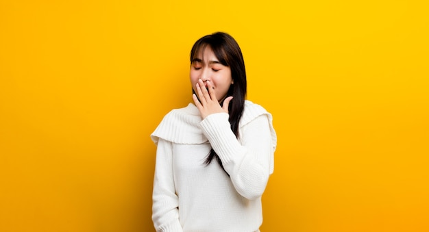Drowsiness. beautiful asian woman. wearing a sweater, sleepy and yawning is tired, covering his mouth with his hands. restless and sleepy