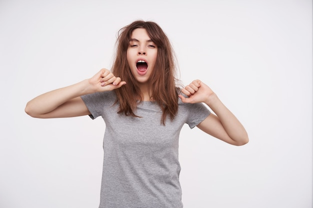 Drowsy young lovely brunette woman with casual hairstyle raising her hands while stretching herself and keeping mouth opened while yawning, isolated on white