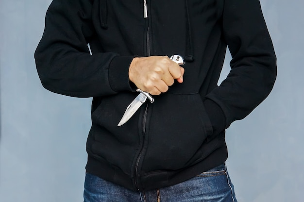 A drug addict burglar in a black hoodie. the concept of the crime of robbery. closeup of a young man hand, holding a knife, about to attack, mafia.