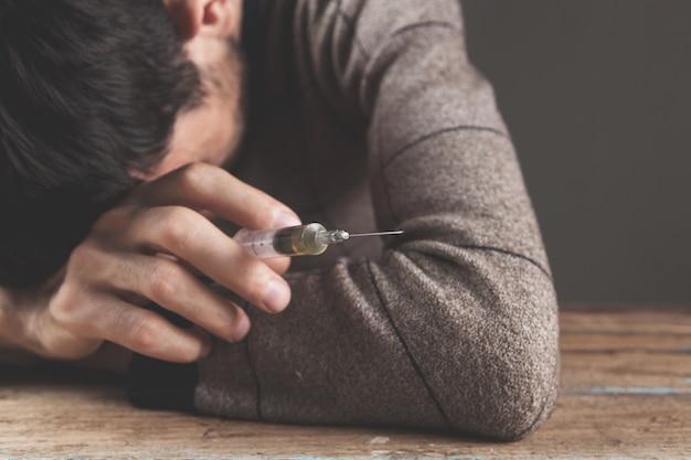 注射器を持っている麻薬中毒者