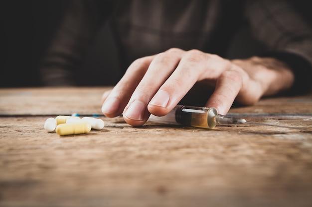 Наркоман держит шприц