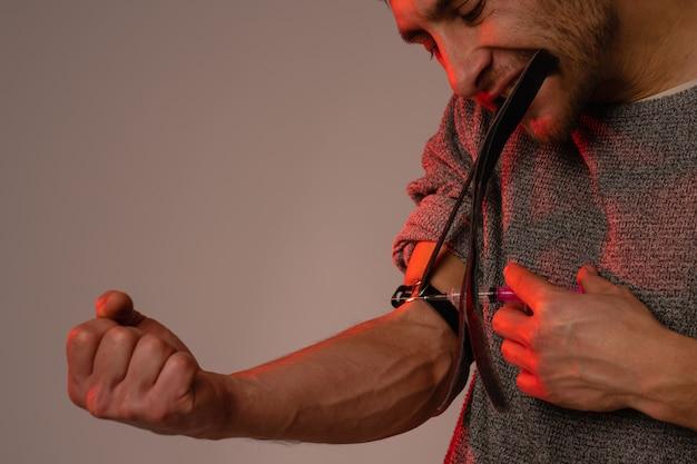麻薬中毒の男性が注射器を手に持って、硬い麻薬の影響に苦しんでいる、麻薬使用者の男性は注射器を静脈に注射し、液体の形でヘロインを取ります。薬物中毒、強迫観念