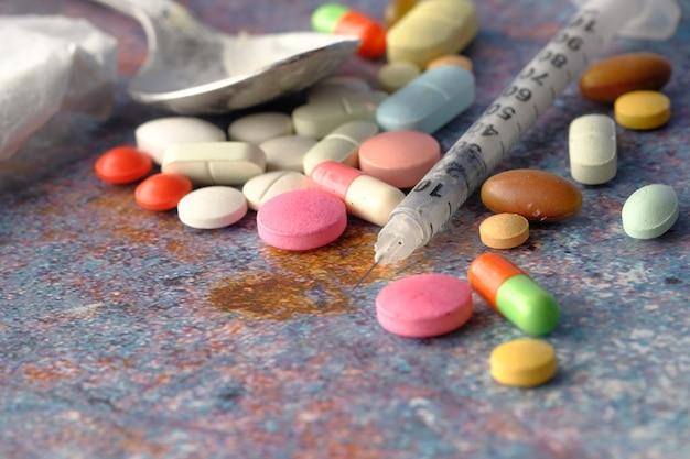 주인공 패킷 및 주사기 블랙 backgrund에 마약 중독 개념.