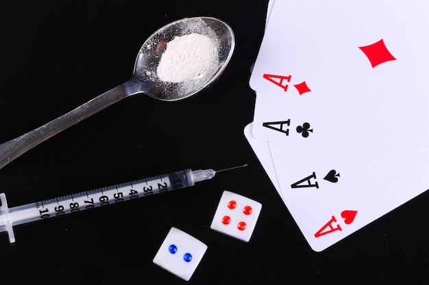 마약 및 도박 중독. 약 가루, 주사기, 주사위, 검은 배경에 격리된 4개의 에이스가 있는 숟가락.