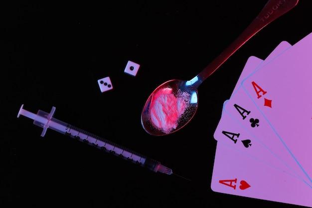 마약 및 도박 중독. 약물 가루, 주사기, 주사위 및 4개의 에이스가 빨간색 파란색 네온 불빛과 함께 검정색 배경에 있는 숟가락