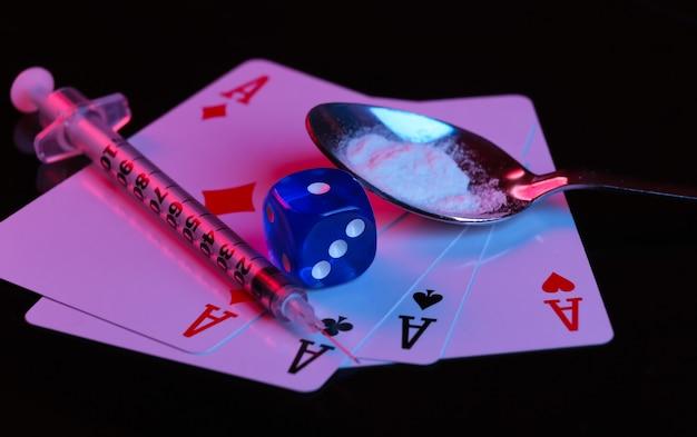 마약 및 도박 중독. 빨간색-파란색 네온 불빛이 있는 검정색 배경에 약물 가루, 주사기 및 4개의 에이스가 든 숟가락