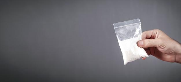 Торговец наркотиками держит кокаин в пластиковом пакете.