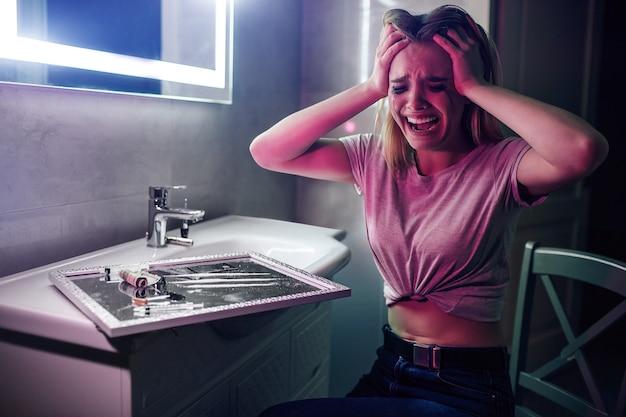 마약 집착과 고통. 마약 중독자는 손에 손을 잡고 마약 근처에서 미쳐 가고 있습니다. 어두운 나이트 클럽의 화장실에서 비명을 지르는 화장이 번진 마약 중독 여성. 싸울 힘 찾기
