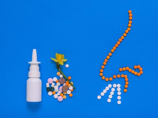 青い背景の鼻と鼻の錠剤の病気の治療のための薬。春の花にアレルギーがあります。鼻やアレルギーの病気の治療の概念。フラットレイ。