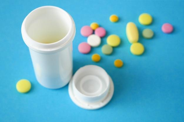 Наркотики, таблетки и капсулы и белая бутылка на синем