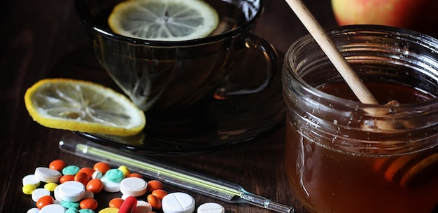 Drugs and pills on a wooden table. various means to prevent colds. tea with lemon and honey. glass cup with tea slice of lemon and a jar of honey.
