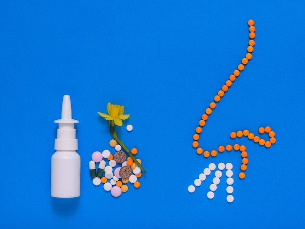 Drugs for the treatment of diseases of the nose and nose tablets on a blue background. allergic to spring flowers. the concept of treatment of diseases of the nose and allergies. flat lay.