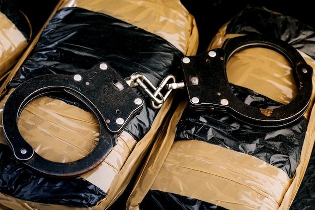 暗い背景に手錠をかけた薬。犯罪の概念。