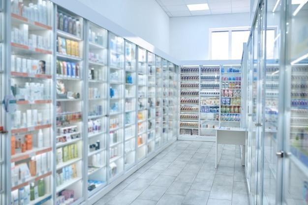 さまざまな医薬品や美容製品で満たされた多数のガラスの陳列棚を備えたドラッグストア