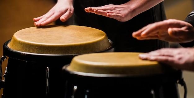 ドラム。ボンボンで演奏するミュージシャンの手。ミュージシャンがボンゴを演奏します