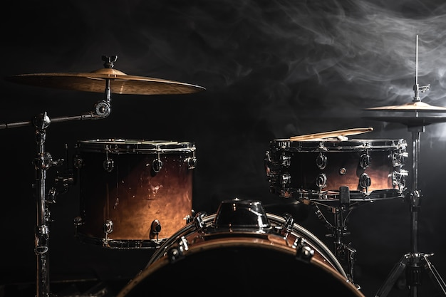 Drum kit on a dark background with stage lighting, copy space.
